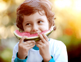 a child happily eating a watermelon